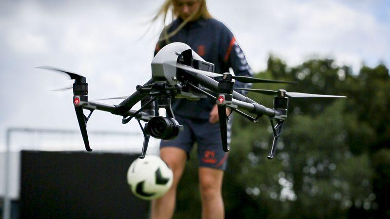 Pige der spiller fodbold mens en drone optager