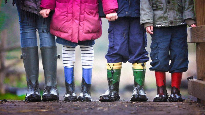 4 børn på række med gummistøvler