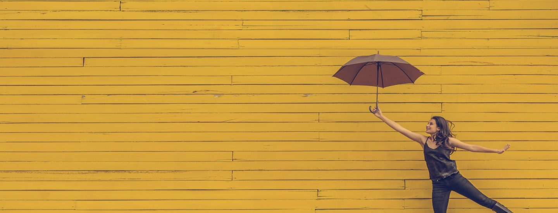 Glad pige med paraply ved gul væg
