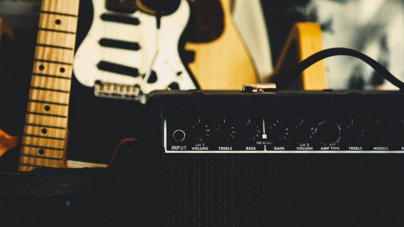Højtaler med guitar i baggrunden