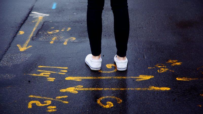 Person der står på asfalt der er tegnet med gult på