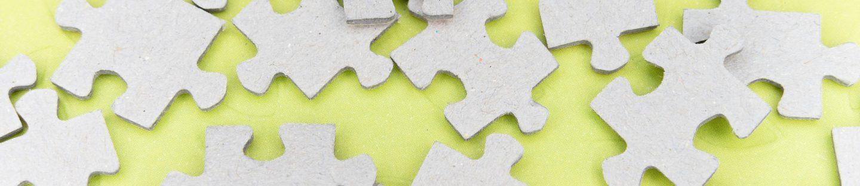 Pap puslespilsbrikker som ligger spredt ud, på gult bord