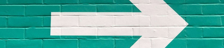 Grøn murstensvæg med hvid pil malet, der peger mod højre.