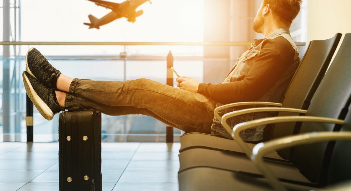 mand sidder i lufthavn og kigger på lettende fly