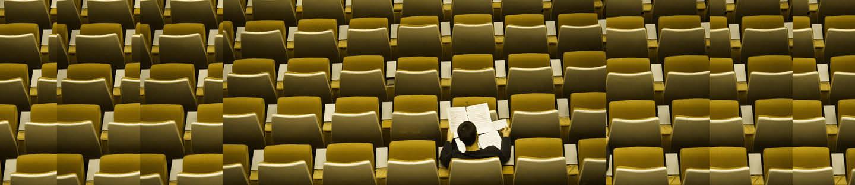 mand læser avis på stolerække med masser af ledige stole omkring sig